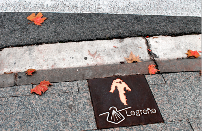 An arrow showing the direction of the camino, with a shell, the symbol of the camino